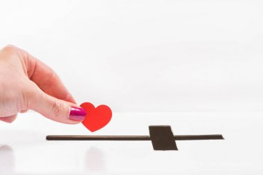 Hand inserting heart into hole for donations