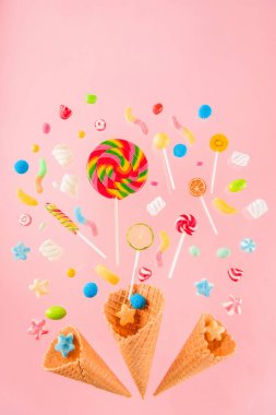 Close-up top view of crispy waffle cones and mix of delicious sweets isolated on pink stock vector