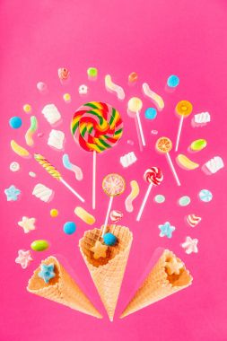 Close-up top view of crispy waffle cones and mix of sweet candies isolated on pink stock vector