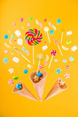 Close-up top view of waffle cones and mix of various sweets isolated on yellow background stock vector