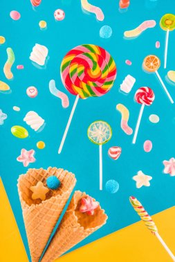 Close-up top view of tasty crispy waffle cones and different colorful candies isolated on blue and yellow stock vector
