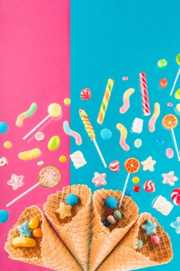Close-up top view of waffle cones and mix of delicious candies isolated on pink and blue stock vector