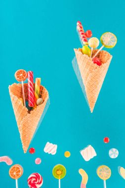 Waffle cones with different delicious jelly candies and lollipops isolated on blue stock vector