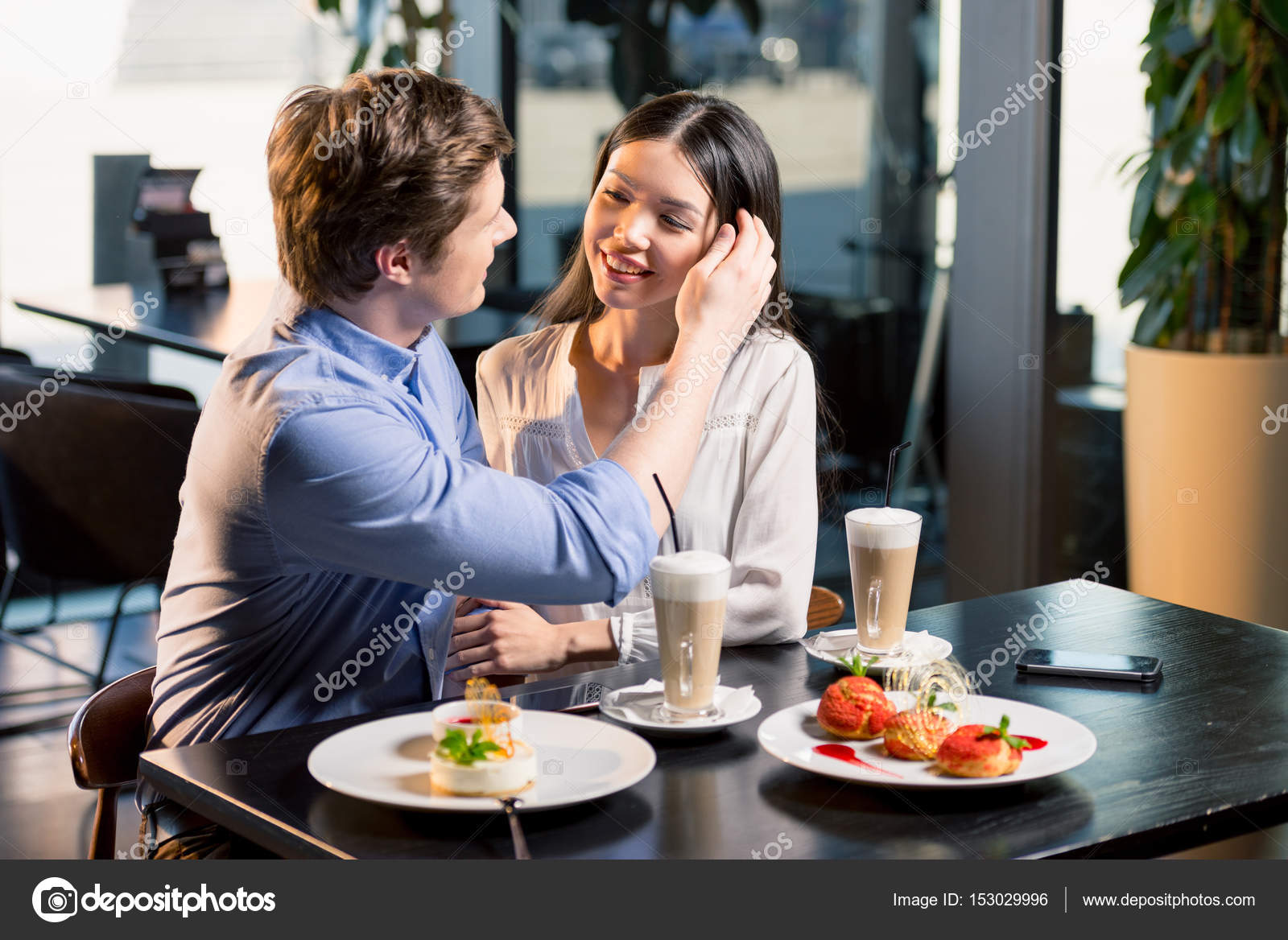 Beautiful happy young couple in love at romantic date in restaurant — Photo  by AndrewTovstyzhenko