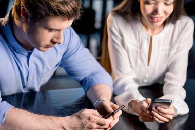 Couple using smartphones