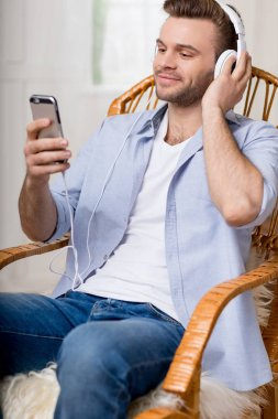 man in headphones using smartphone