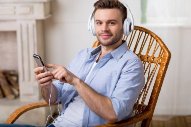 Portrait of smiling man in headphones using smartphone and looking to camera stock vector