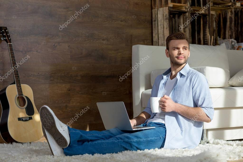 Young man with laptop and cup
