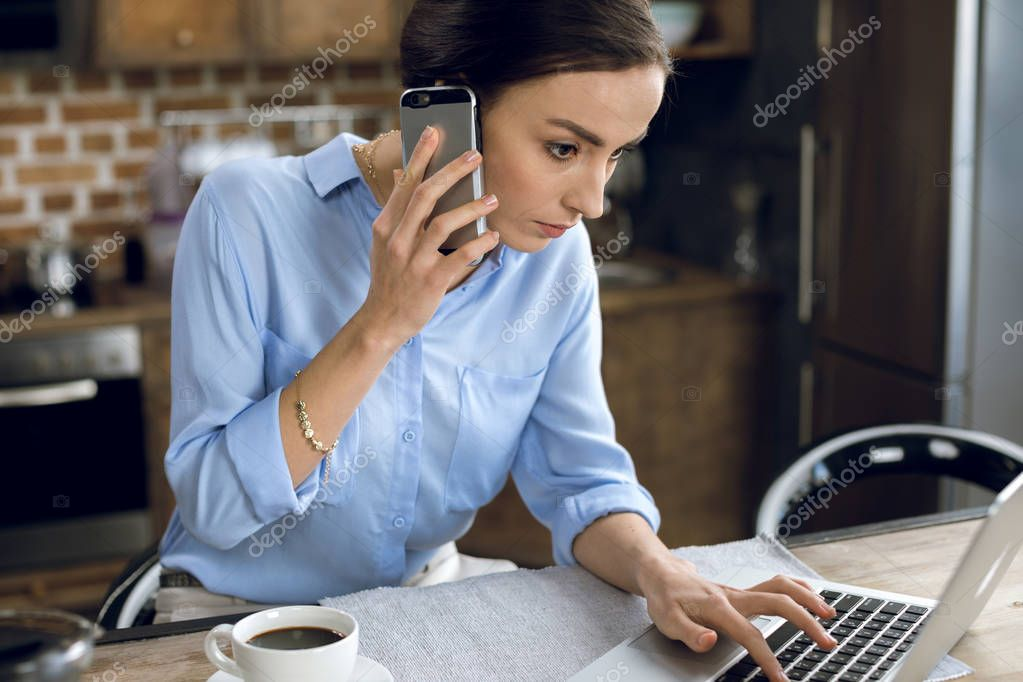 Woman using laptop and smartphone