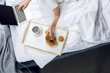woman using laptop in bed