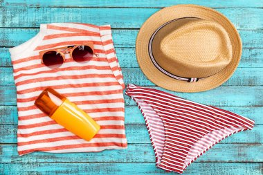 Top view of straw hat, sun cream, swimming pants and sunglasses on table stock vector