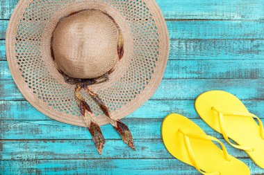 Top view of straw hat and yellow flip-flops on blue wooden table, summer concept stock vector