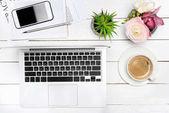 Laptop a šálek kávy na stole
