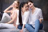 usmívající se mnohonárodnostní dívky sedí na podlaze