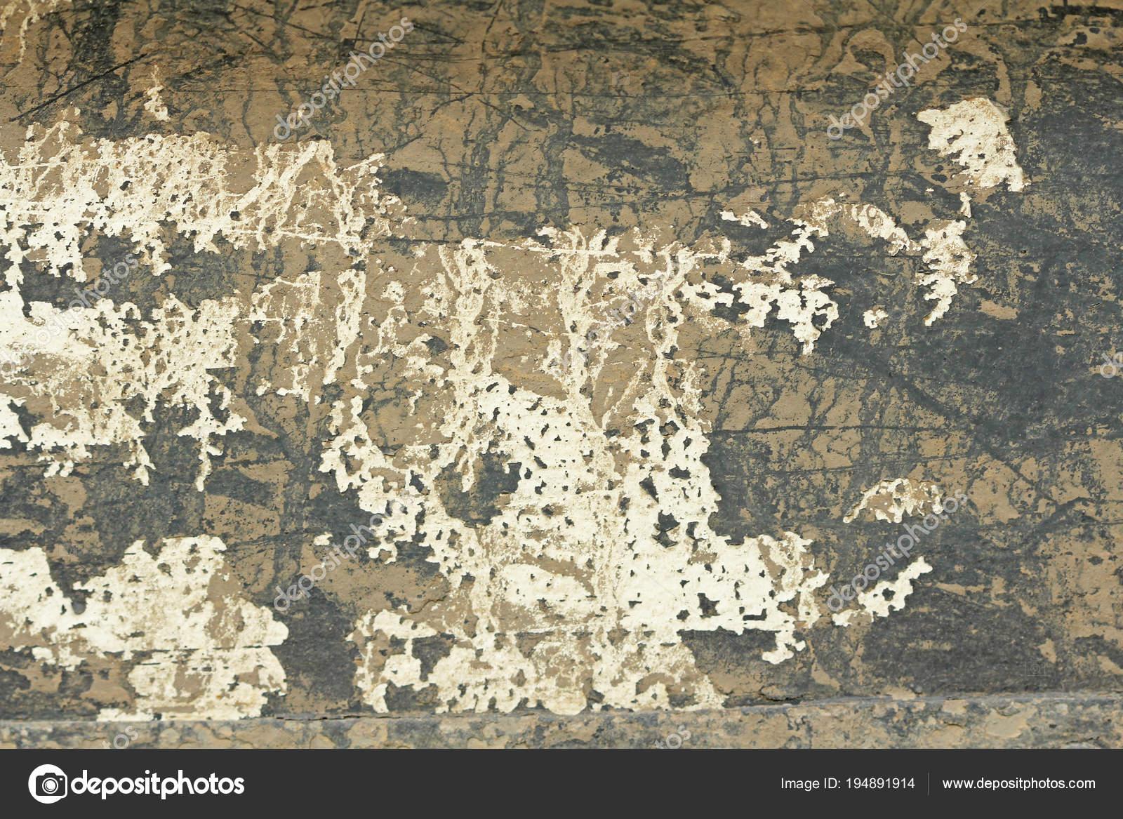 Oude schilferige verf peeling uit een grungy gebarsten muur