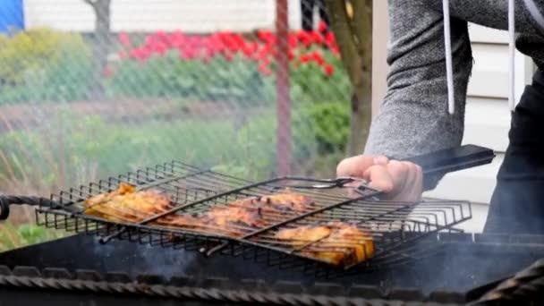 Erős férfi jobb kézzel főz csirkehúst a grillen, és hússal megfordítja a grillt. Barbecue hús főzés faszénen a természetben tavasszal és nyáron.