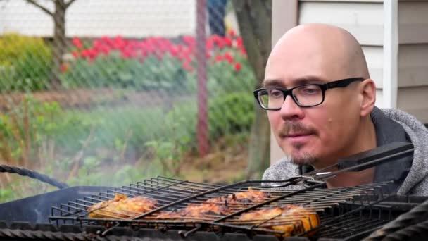 Oroszország, Moszkva, 2019. május 11. Egy kopasz fiatalember bajusszal és szakállal, fekete peremű PRADA szemüvegben, húst főz a grillen, legyezi a hőt és a tüzet, és megfordítja a húst a grillen..