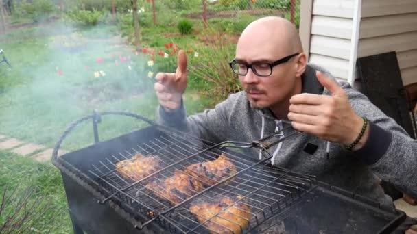 Mladý pohledný plešatý muž v brýlích s černým rámem, vaří kuřecí maso na uhlících, na grilu, grilování. Muž kontroluje připravenost masa, čichá kouř a páru, která stoupá z masa.