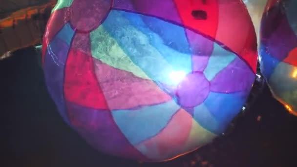 Große Plastikblasen auf dem Wasser für Kinder. Zorbing im Schwimmbad. Bunte bunte, blaue und rote Luftballons. Nachtlicht. Lieblingsaktivitäten für Kinder im Wasser. Nachtreflexion im Wasser.