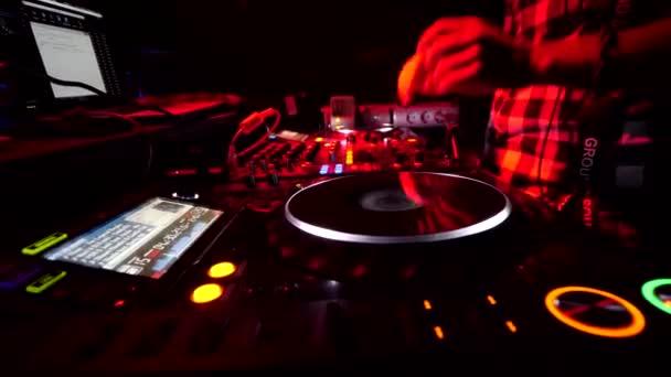 Rusko, Tver, 7. srpna2019. Ruce DJ zblízka. Kolem blikají rozmazaná barevná světla. DJ přehrávání hudby na mixéru na vinylu nebo disku na barevném rozmazaném pozadí.