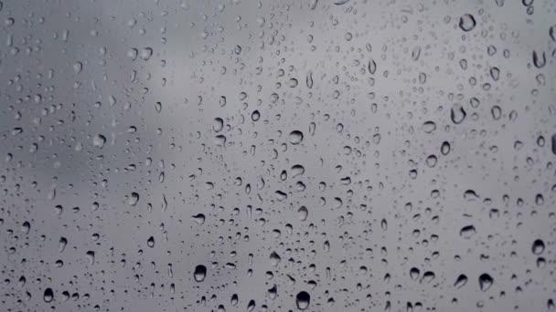 Dešťové kapky na okno. Oknem stékají kapky deště. Kapky vody nebo kapky deště kapky na okenní sklo s rozmazanými budovami pozadí. Smutek, touha, otupělost, podzimní deprese, chmury.