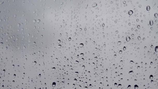 Esőcseppek az ablakon. Egy csepp eső folyik le az ablakon. Vízcseppek vagy esőcseppek az ablaküvegen homályos épületek hátterével. Szomorúság, vágyakozás, unalom, őszi depresszió, komor.
