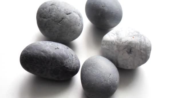 Detailní šedé kulaté kameny se otáčejí na světle šedém pozadí. Obyčejné šedé oblázkové kameny. Pozadí pro meditaci a relaxaci.