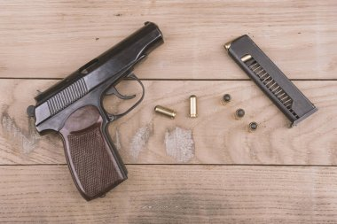 Traumatic pistol with bullets and cartridge on the wooden surface