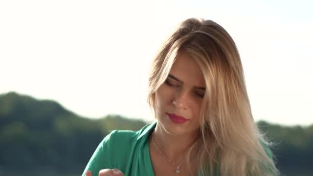 Zblízka portrétní krásná blond dívka v zelených šatech