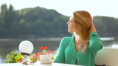 Attractive girl with big eyes drinks coffe in summer restaurant near the water