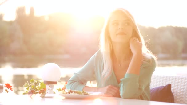 Étterem pincér hozza a számlát szőke lány. Nyári naplementében a folyó