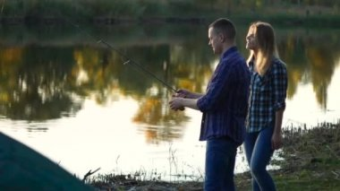 Happy young couple at lake pike fishing