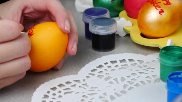 Painting an orange Happy Easter egg