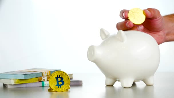 Mans hand put Bitcoin cryptocurrency into white pig moneybox near Dollars and Euros on the white background