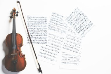 Full length violin and bow on sheet music background. Music concept