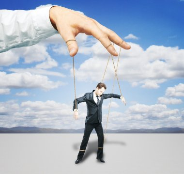 Hand controlling businessman as puppet on sky background. Control concept