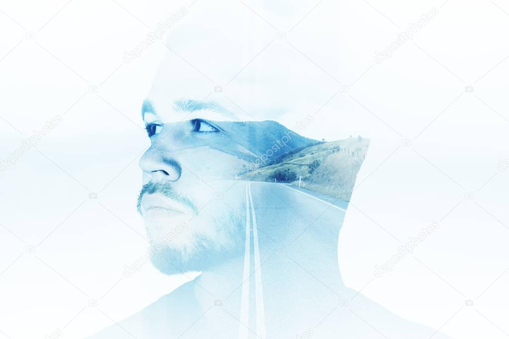 Side portrait of handsome young man on abstract blue landscape background. Thoughts concept. Double exposure