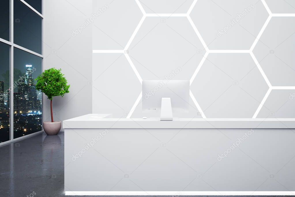 modern reception desk with computer in interior with honeycomb pattern on wall decorative plant and