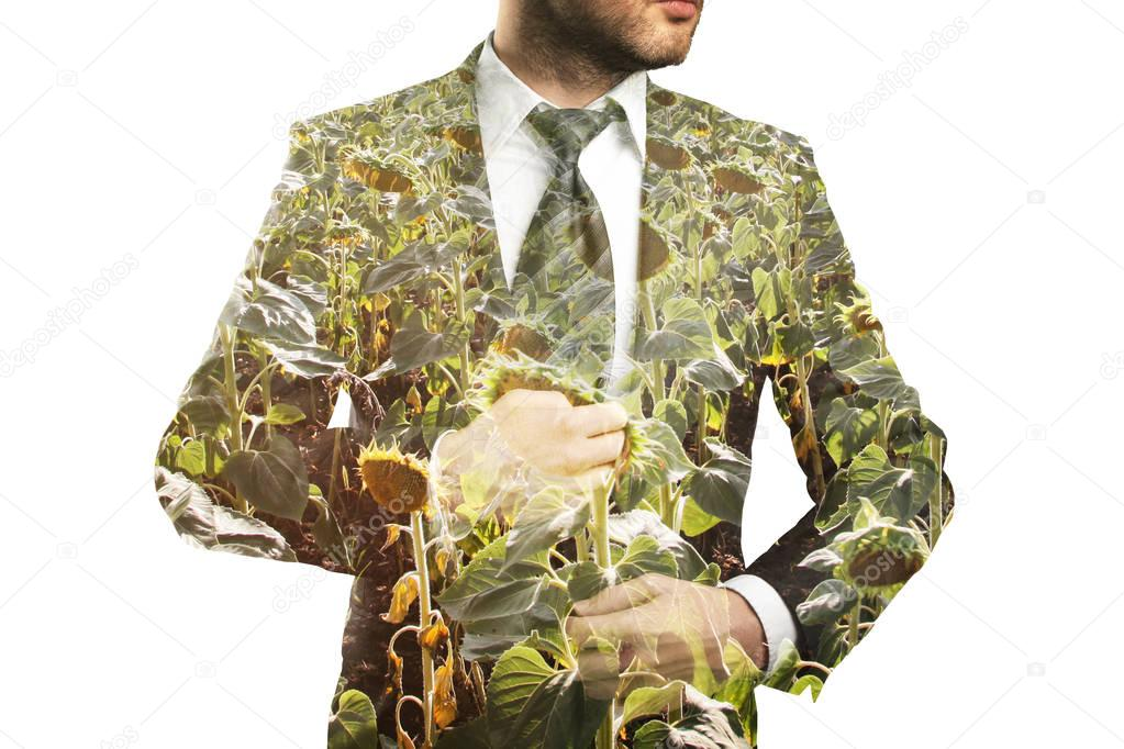 Young businessperson in suit on sunflower field background. Agriculture concept. Double exposure