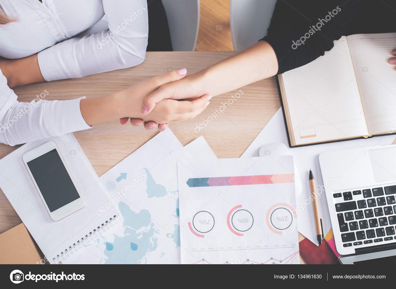 Draufsicht Der Zwei Weißen Frauen Händeschütteln An Schreibtisch Mit  Finanzberichte Und Andere Gegenstände. Partnership Konzept U2014 Foto Von  Peshkova