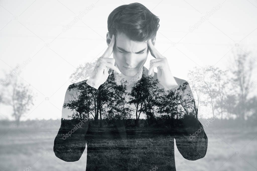 Pensive young male on dull landscape background. Apathy concept