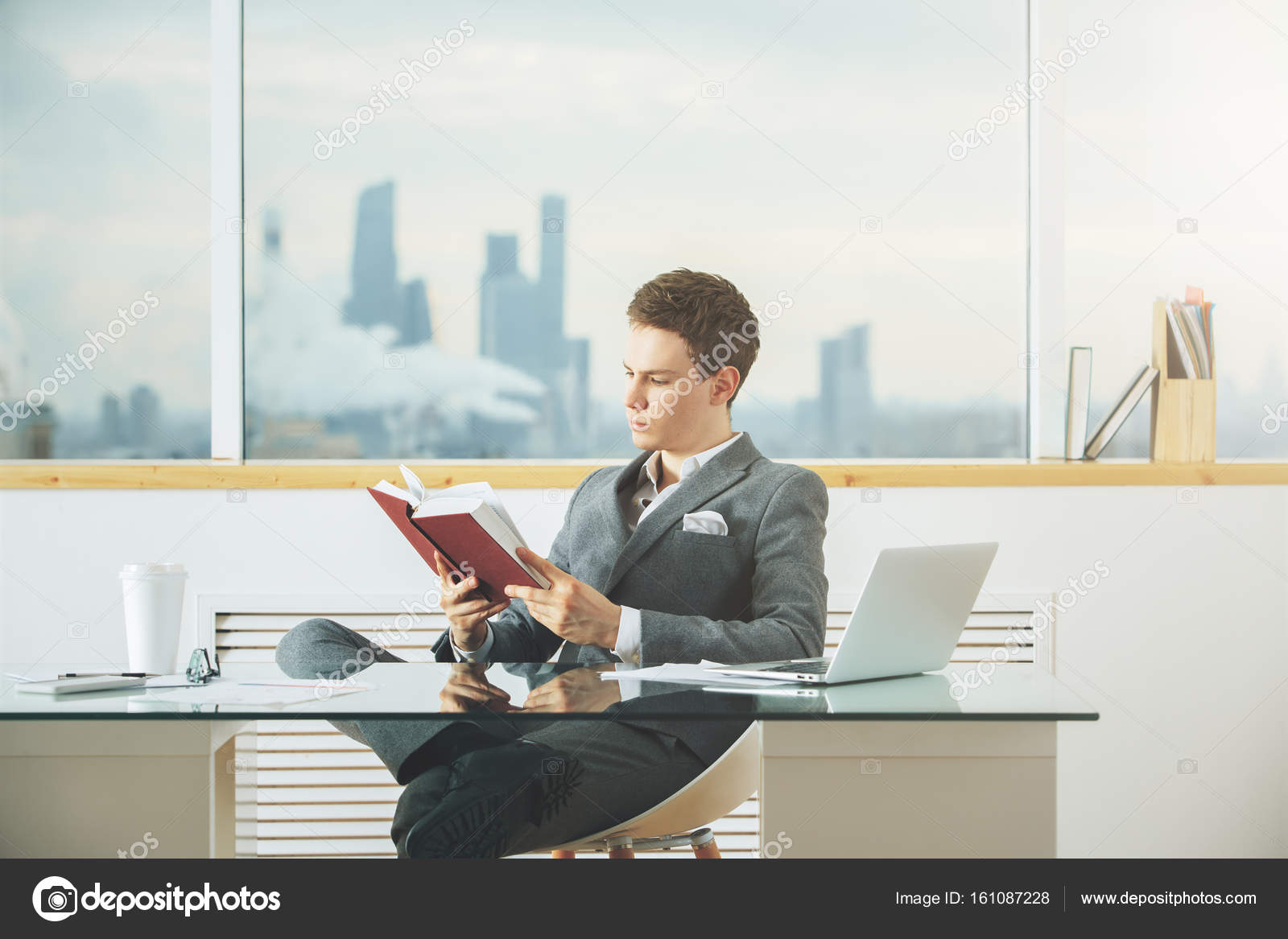 european cup office coffee. Focused Young European Student Reading Book At Desktop With Laptop, Coffee Cup And Other Items Office S