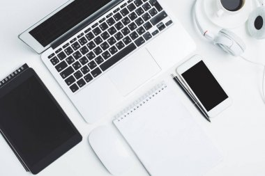 White desktop with devices and supplies