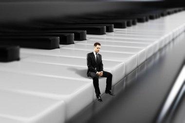 Businessman sitting on piano keys