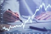 Dvojnásobná expozice ženské ruky si dělá poznámky s hologramem Forex. Koncepce analýzy akciových trhů.