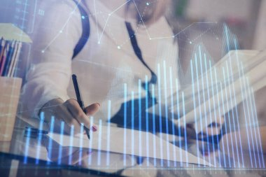 A woman hands writing information about stock market in notepad. Forex chart holograms in front. Concept of research.