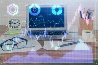 Double exposure of chart and financial info and work space with computer background. Concept of international online trading.