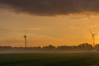 wind wheels at sunrise and fog with dark clouds