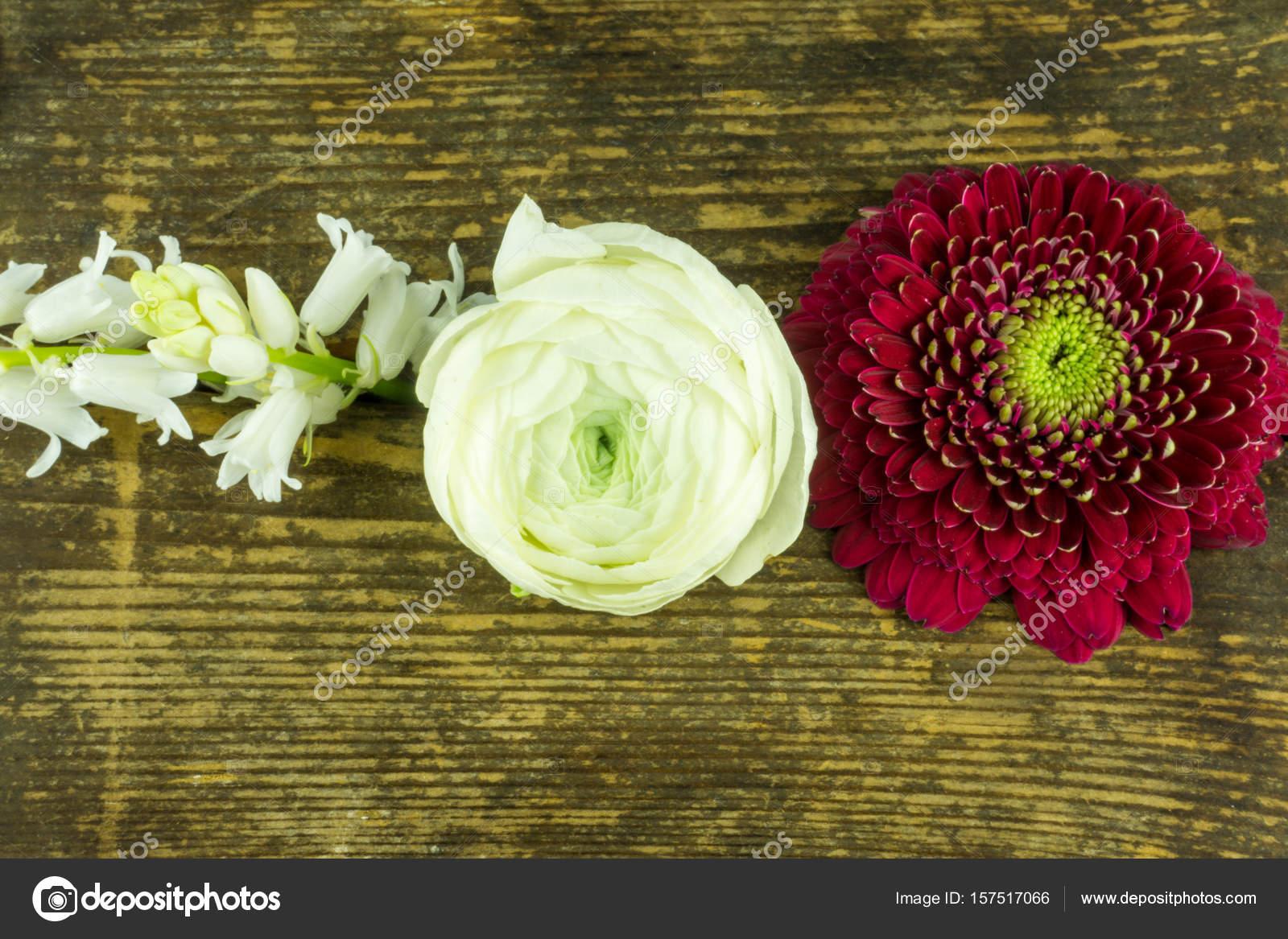 Blumen in vielen verschiedenen Farben auf einem rustikalen Holztisch ...
