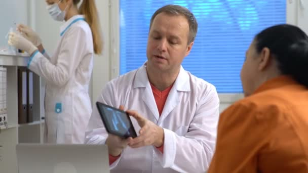 Handsome medical doctor is showing to female patient a X-ray picture on tablet
